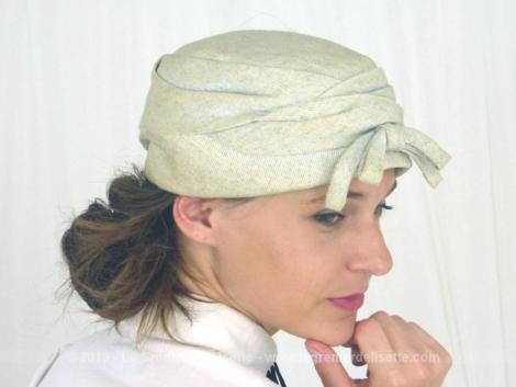 Ancien chapeau tissus avec petit noeud sur le devant avec une forme tambourin date des années 50/60. Il est en tissus chamarré beige clair et beige foncé.