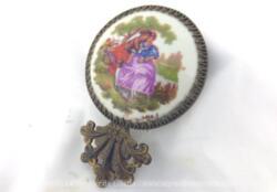 Petit face à main écusson porcelaine en métal doré avec d'un coté un miroir serti et de l'autre un écusson en porcelaine de Limoges.