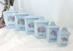 Six anciens pots à épices bleu pastel de tailles décroissantes au dessin de fleurs et estampillé par un numéro.