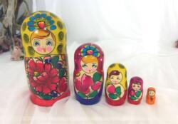 Jeu de 5 grandes poupées russes aux fleurs sur fond de rouge et jaune.
