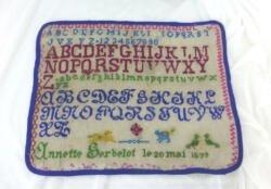 Ancien grand abécédaire d'écolière de 1899 de 34 x 28 cm, brodé au point de croix en fils de différentes couleurs avec 4 alphabets entiers et signé de la jeune brodeuse assidue Annette Gerbelot et 20 mai 1899.
