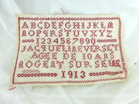 Ancien abécédaire d'écolière de 1913 de 25.5 x 16.5 cm, brodé au point de croix en fil rouge avec l'alphabet et les chiffres.... mais aussi avec le nom, l'age et la ville de l'écolière bien assidue ainsi que l'année.