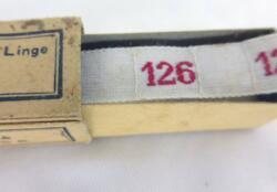 """Ancien ruban avec le chiffre 126 brodé et sa boite en carton portant les inscriptions """"M.D. Marque de qualité - Fabrication Française - Initiales & Chiffres pour Marquer les Linge """"."""