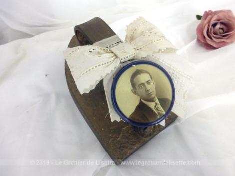 Ancien fer à repasser noeud dentelle et écusson, revisité par une douce patine mordorée et un noeud supportant un écusson porte-photo du portrait d'un homme du début du siécle dernier.