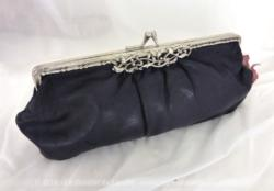 Belle pochette en cuir noir avec fermoir décoratif et en forme de porte-monnaie.