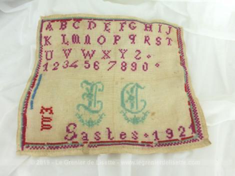 Ancien abécédaire d'écolière de 1921 de 25 x 21.5 cm, brodé au point de croix en fil rouge avec l'alphabet, chiffres,... mais aussi avec les monogrammes, ville et l'année du travail d'une écolière bien assidue.