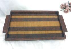 Voici un plateau des années 60/70 avec un bois teinté imitation loupe d'orme dont le plateau central, décoré par deux variétés de bois, est vitrifié.