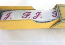 """Ancien long ruban avec lettres FJ brodées et sa boite en carton portant les inscriptions """"""""Initiales - Tissées Rouge Grand teint - Pour marquer le linge - etc - Economie - Rapidité """" - """"The Household Gem - Linen Markers"""" ."""