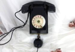 Ancien téléphone bakélite avec son cadran et son écouteur à suspendre sur un mur avec plaque P et T et datant de 1962.