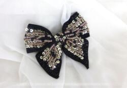A partir d'un ruban en reps, voici une belle broche, faite à la main et représentant une belle ganse, décorée de sequins couleur argent et de perles de rocaille en verre de couleur soit irisée soit noire.