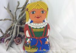 Voici une poupée chiffon coussin représentant une petite fille portant un panier de cerises et un grand noeud bleu dans ses cheveux blonds de 40 x 24 x 12 cm.