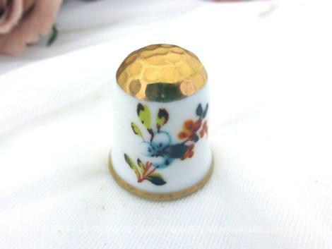 Un superbe dé à coudre porcelaine aux fleurs et dorures peintes à la main. Le dessin représente de chaque coté, un bouquet de fleurs.