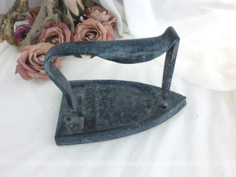 """Sur une patine noire, un légère touche de gris donne un effet vieilli à cet ancien fer à repasser en fonte de presque 1 kg avec en relief le texte """"Le Parisien"""" ainsi que le numéro """"5"""". Pour une déco très shabby !"""