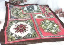 Foulard de la marque Ted Lapidus, joli carré de 76 x 76 cm en tissus 100 % polyester, identique à de la soie aux couleurs rose, fuchsia, noir et marron où mélangent bien les dessins de volutes noires sur fond blanc.