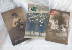 Trois cartes anciennes d'enfants souhaitant la Bonne Année sur des photos sépia datant du début du siècle dernier.