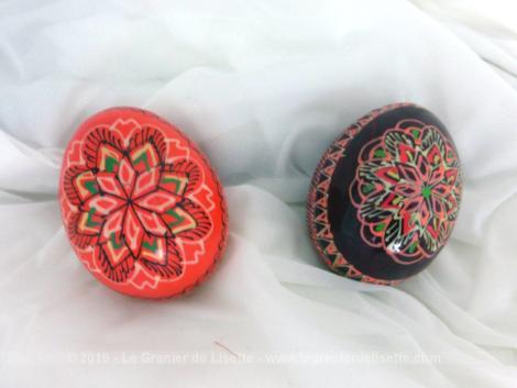 Voici deux œufs en bois de 6.5 cm x 5 cm. Ils sont décorés de volutes et arabesques dans des tons dominants de rouge.