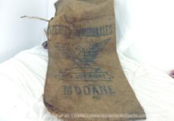 """Ancien sac en toile de jute épaisse, portant l'inscription """"Riz Piémont"""" et le dessin d'un phénix. Avec de nombreuses marques de reprises, couture et trous. Du pur authentique."""