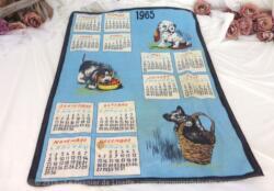 Ancien torchon calendrier 1965 de 60 x 46 cm sur fond bleu pastel avec en décoration des chiens qui s'amusent.