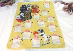 Ancien torchon calendrier 1968 de 60 x 46 cm sur fond jaune paille avec en décoration des chiens qui s'amusent.