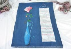 Ancien torchon calendrier 1969 de 60 x 47 cm sur fond bleu lagon avec en décoration un grand vase soliflore et une rose.