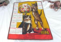 Ancien torchon calendrier 1974 de 58 x 45 cm sur fond rouge avec en décoration deux chats qui jouent avec un aquarium.