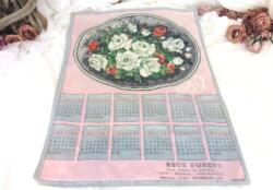 Ancien torchon calendrier 1969 de 60 x 47 cm sur fond rose avec en décoration un grand écusson ovale rempli d'un bouquet de roses .