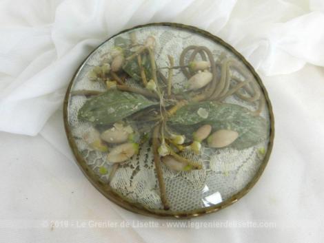 Petit cadre rond bombé aux fleurs de cire, anciens vestiges d'une décoration d'une couronne de mariée.