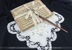 Composition shabby autour de la musique, avec d'anciennes partitions cartonnées, un mouchoir de mariée, un pince nez et un porte plume. Décoration unique.