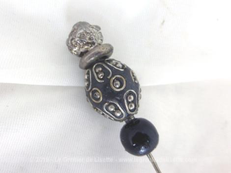 Sur 12 cm, voici une épingle à chapeaux, création unique, composée de 4 perles ciselées de différentes formes en verre ou métal sur 4.5 cm de long.