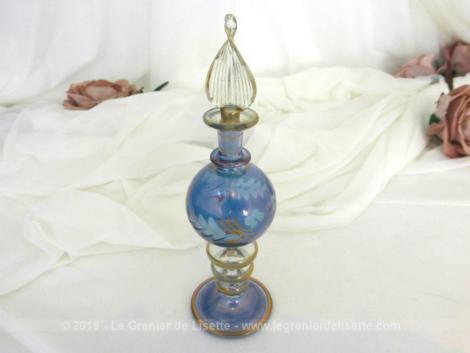 Sur 14 cm de haut, voici un fiole bleue en verre soufflé de forme ronde de couleur bleu irisé et décorée de fleurs en verre dépoli et de dorures.