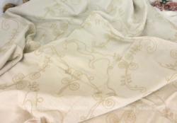 Voici un coupon de tissus en toile écru légère brodé de volutes et d'arabesques. Il mesure 138 x 160 cm. Les broderies en fils épais sont en relief.