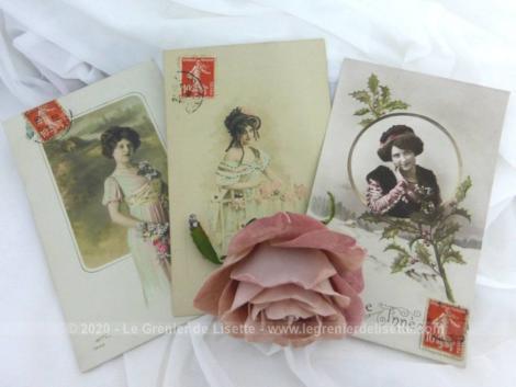 Quatre anciennes cartes postales sur papier glacé représentant des portraits de femme portant des fleurs le tout sur fond blanc.