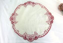 Ancien napperon rond de 35 cm de diamètre en lin décoré brodés en rouge sur tout le pourtour et qui prend la forme des fleurs mises en valeurs par les broderies.