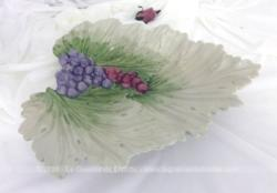 En forme de feuille de vigne, voici une coupe de fruits en céramique façon barbotine avec des grappes de raisin en relief sur 28 cm x 33 cm et 4 cm.