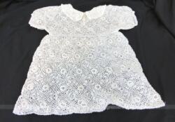 Petite robe fait main au crochet en fil de coton blanc, avec col rond et petites manches courtes, prévue pour fillette ou poupée.