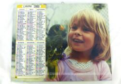 Ancien almanach des P.T.T. de 1988 avec d'un coté la photo d'une fillette avec une perruche et un bébé avec un ours bleu de l'autre. Il y a 12 feuillets supplémentaires.