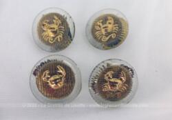 Quatre boutons en verre décorés d'un crabe en métal doré en relief sur le dessus et une rondelle en laiton dessous .