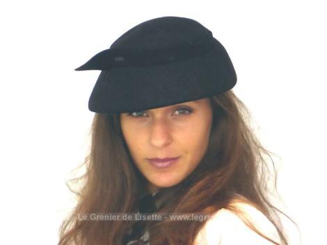 Ancien chapeau bibi des années 40 en feutre noir décoré sur le pourtour par un ruban se terminant par un ergot rigide en relief. Très vintage.