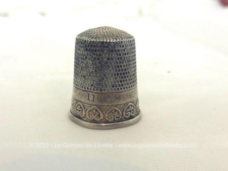 Voici un dé à coudre de collection en argent avec une bordure décorée d'une guirlande de volutes .