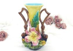 Ancien vase en barbotine numéroté et signé, décoré d'un lys rose en relief au centre, avec un col couleur ocre et intérieur bleu pastel et des anses marrons originales qui en soulignent toute l'harmonie.