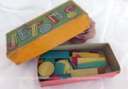 Voici une ancienne boite en carton remplie de jetons de jeu en bois de différentes formes, ronds ou rectangulaires et couleurs bleu, rouge, jaune. et vert.