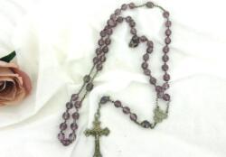 Voici un ancien chapelet aux perles de verre à facettes de couleur mauve avec croix et médaille ouvragées en métal argenté.