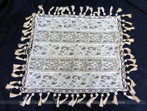 Voici un napperon de 35 x 29 cm réalisé à la main par des bandes successives de dentelle fine cousues entre elles et décoré de délicats pompons.