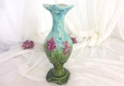 Voici un ancien vase en barbotine numéroté et décoré de fleurs d'iris fuchsia avec un col bleu pastel et un socle vert d'eau. Très tendance shabby !