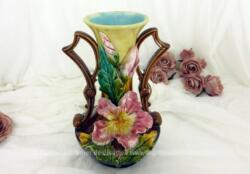 Ancien vase en barbotine numéroté et signé, et décoré de 3 iris roses en relief , de couleur ocre et intérieur bleu pastel avec des anses marrons originales.