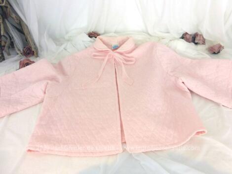 Ancienne liseuse de couleur rose en nylon avec manches larges et rubans pour fermer.