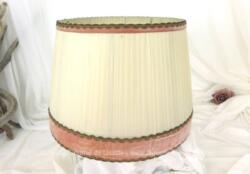Voici un abat jour vintage habillé par des bandes de plastique et décoré de rubans velours rose