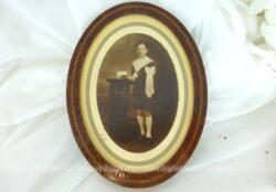 Cadre ancien ovale en bois de loupe avec une photo en sépia d'un communiant avec beaucoup de charme .