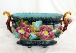 Voici une superbe et ancienne jardinière en barbotine aux belles couleurs et décorée de belles fleurs en relief de passiflores. Numéro et gravure sous le socle.