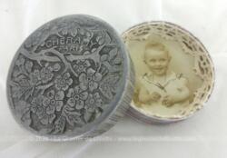 """Poudrier en aluminium de la marque """"Cheramy Paris"""" en deux parties, une avec un miroir et l'autre revisitée en porte photo avec la photo d'un bébé et décorée de dentelle. Pièce unique."""